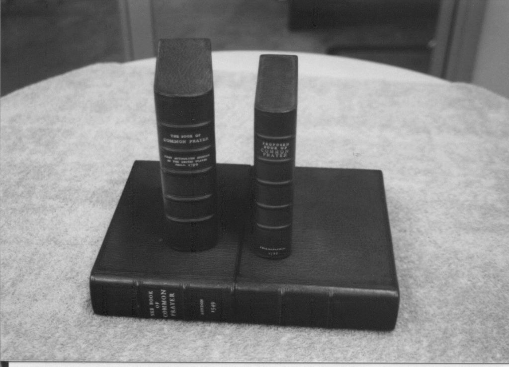 Three of the 1st american book of common prayers stacked on a table.
