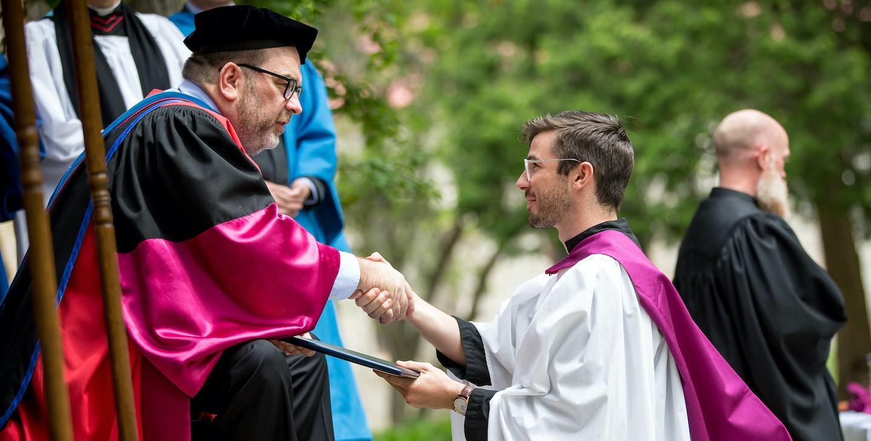 A student getting his diploma at graduation.