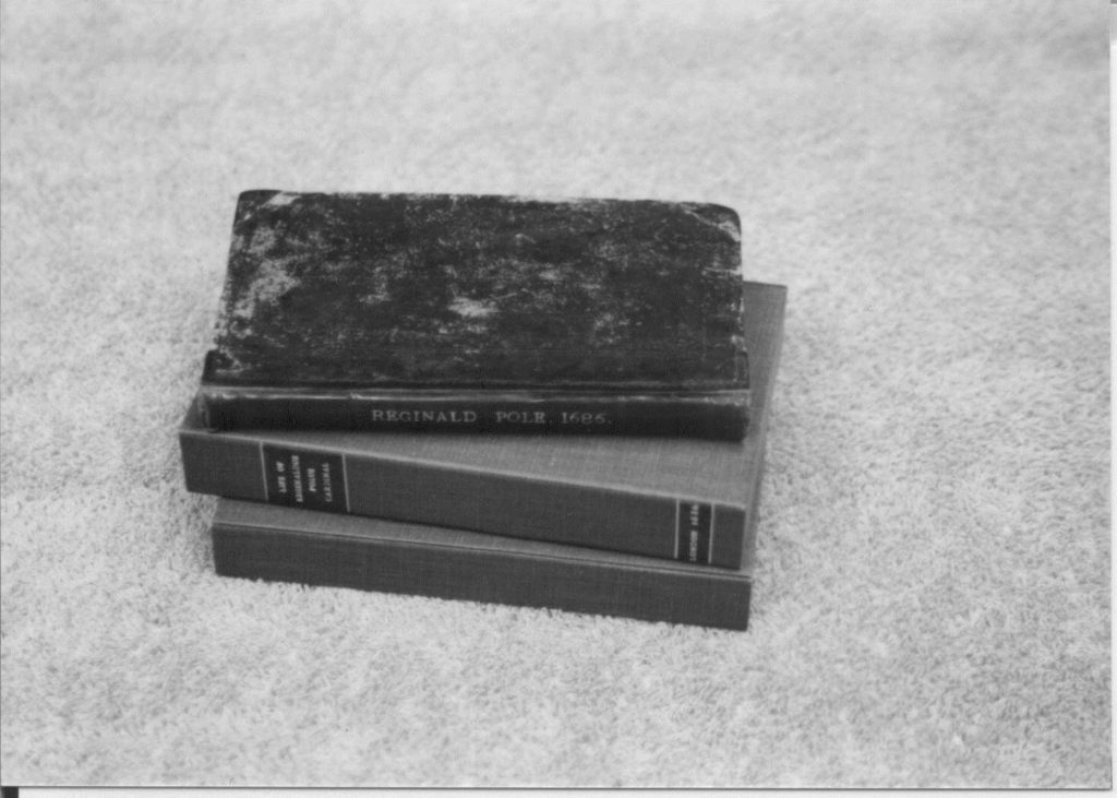 Three books about the life of reg. polus cardinal stacked on a table.