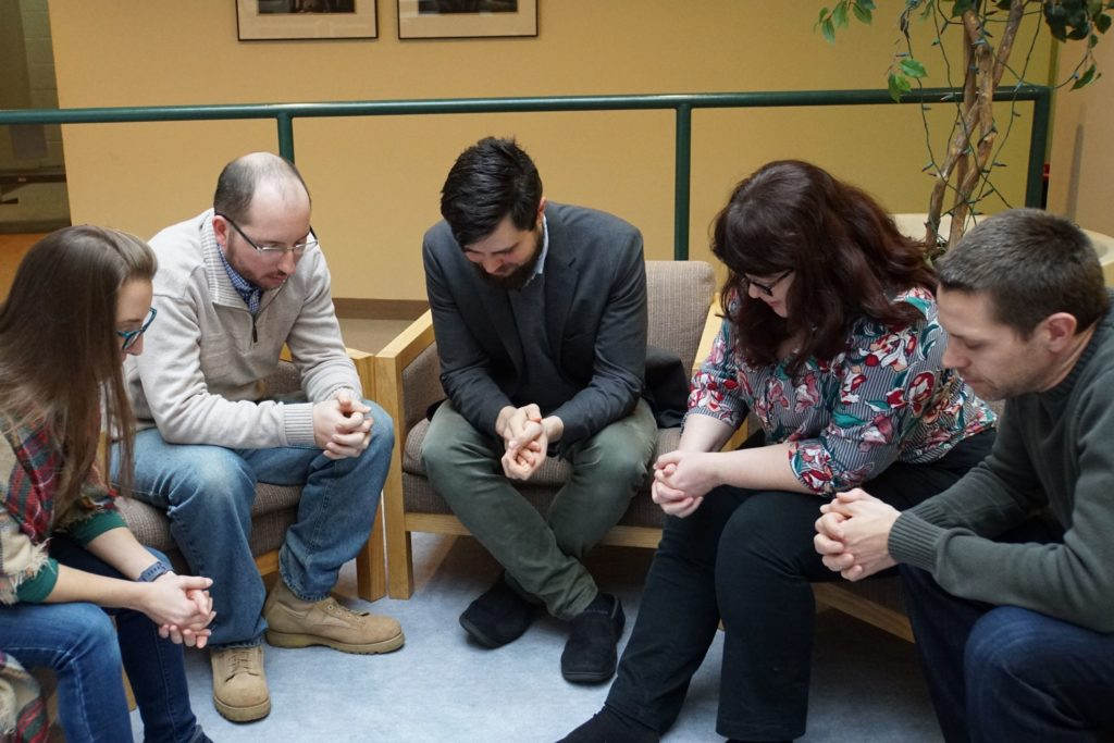 A group of people praying together.