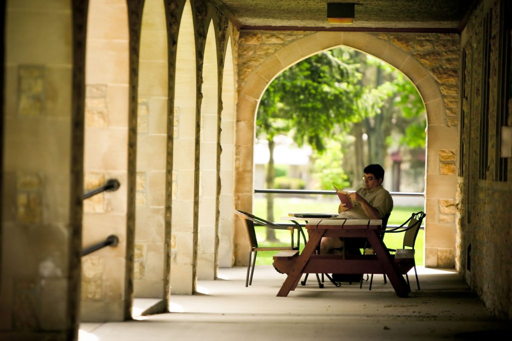 A seminary student reading outside.