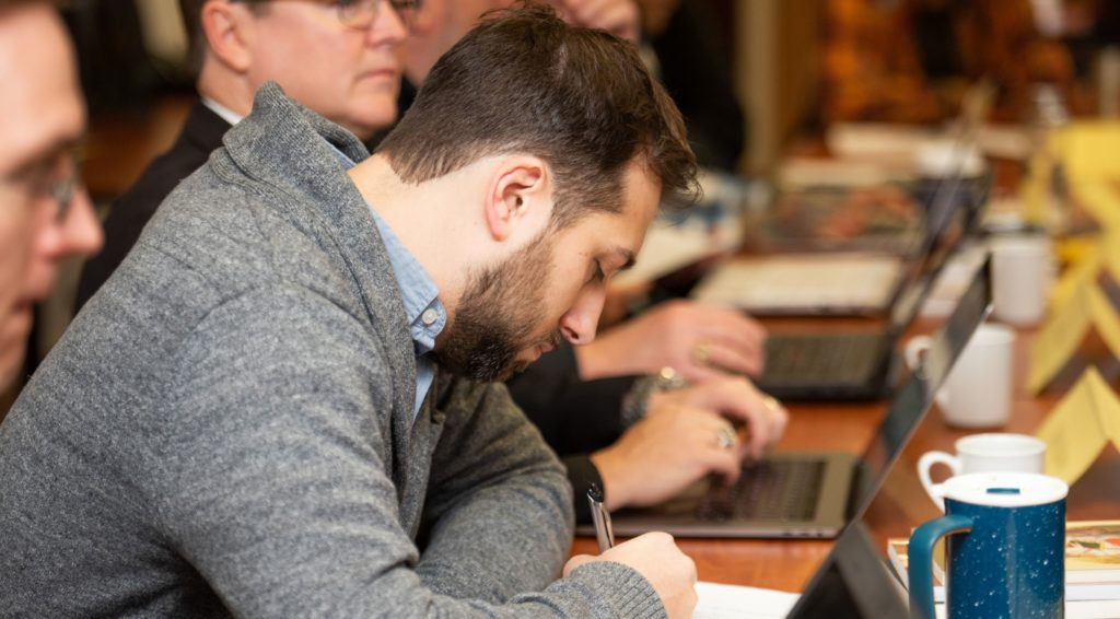 A student taking notes during an advanced degree program class.
