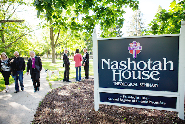 The nashotah house sign with people walking by.